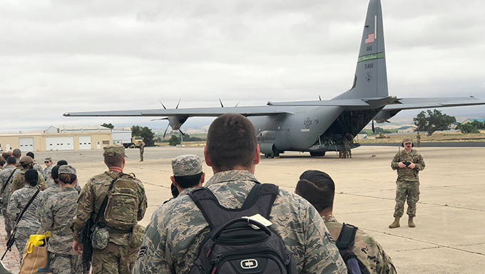 California Air National Guard personnel from the 146th Airlift Wing prepare to board a C-130J Super Hercules military aircraft with it's ramp door down on a flight line at the Paso Robles Municipal airport.