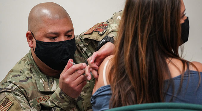 A U.S. Air National Guard medical technician places a syringe containing the COVID-19 vaccine into the arm of a military dependent inside a medical facility.